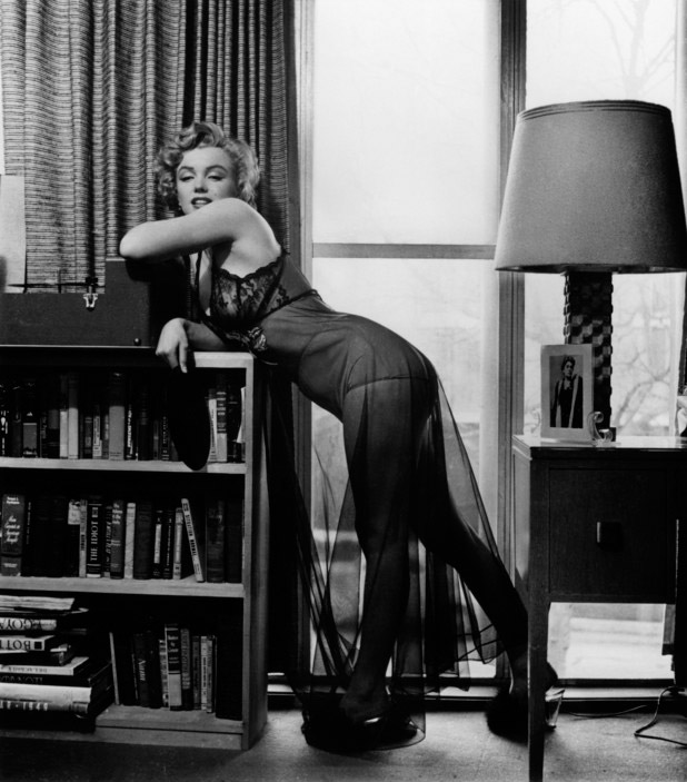 USA. US Actress Marilyn MONROE posing in her two bedroom apartment. Under the lamp is a picture of Italian actress Eleonora DUSE, whom Marilyn MONROE admired greatly. 1952