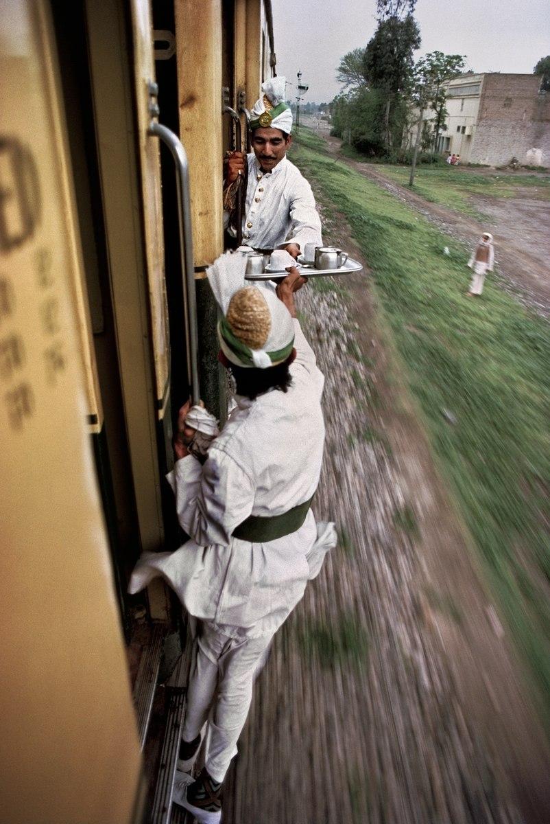Официанты передают друг другу утренний чай между вагонами на железной дороге в Пакистане.
